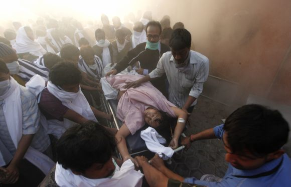 Rescuers carry a patient on a stretcher out of AMRI hospital after it caught fire in Kolkata