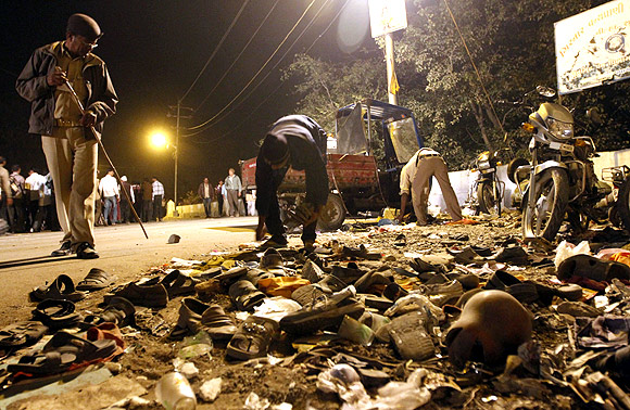 A man collects shoes left behind during a stampede in Junagadh district, in Gujarat