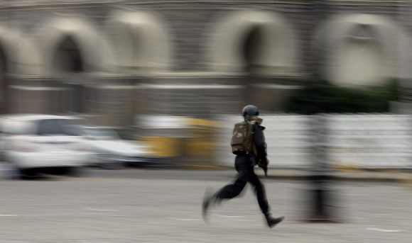 A commando shields himself with a stone slab during a gun battle at the Taj Hotel in Mumbai during 26/11 attacks