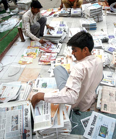 Distributors sort through newspapers before selling them in Noida, UP