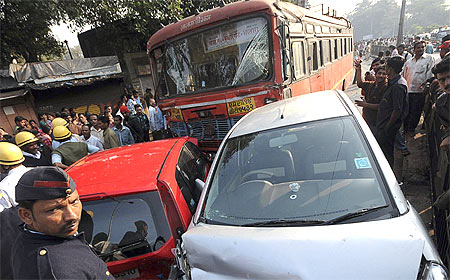 Onlookers and rescue workers gather around the bus and other vehicles after the Pune tragedy