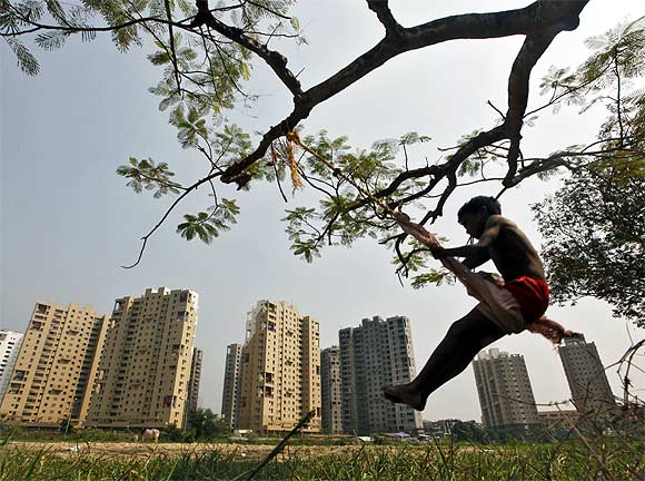 A boy plays in front of a residential estate in Kolkata