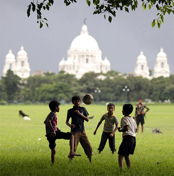 Children play soccer on a field in front of the Victoria Memorial