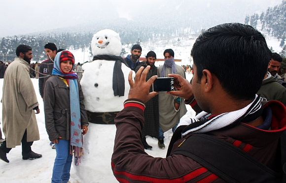 A tourist poses with a snowman