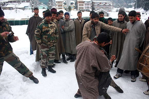 Youth wrestle on snow as Army jawans look on
