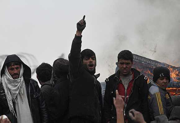 An Afghan man shouts anti-US slogans near a pile of wood and tyres, set on fire by the protesters, during a protest outside the U.S. military base in Bagram, north of Kabul
