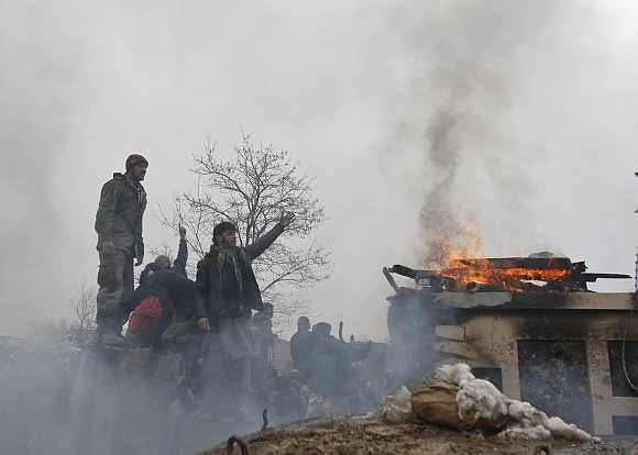 Afghan men shout anti-US slogans near a pile of wood and tyres, set on fire by the protesters, during a protest outside the US military base in Bagram
