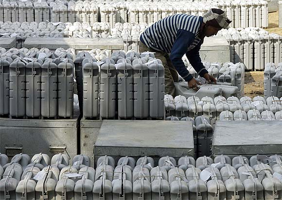 A polling official collects electronic voting machines from a distribution centre