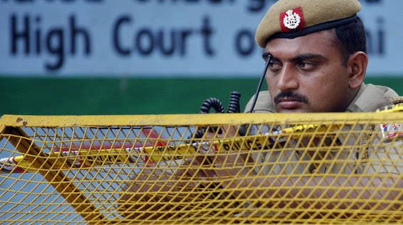 A policeman keeps guard from behind a barricade outside the high court after a bomb blast in New Delhi