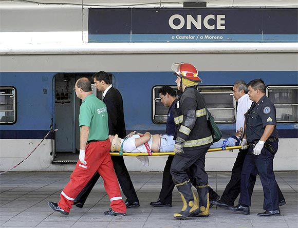 Rescue workers carry a wounded passenger from the commuter train