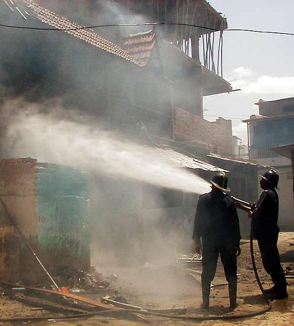 Firefighters try to extinguish a burning building set on fire by rioters in Ahmedabad on May 10, 2002