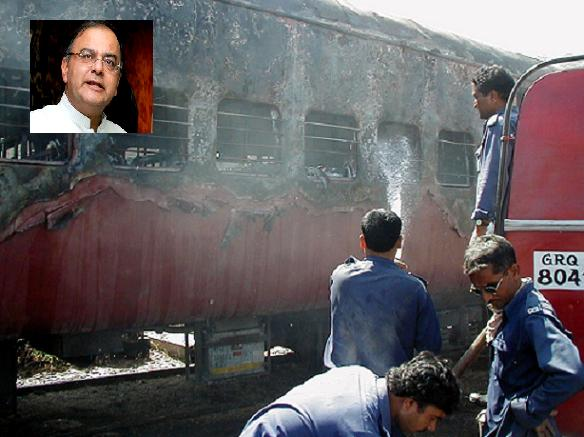 Firemen try to put out a fire on the Sabarmati Express in Godhra, Gujarat February 27, 2002. Inset: Arun Jaitley