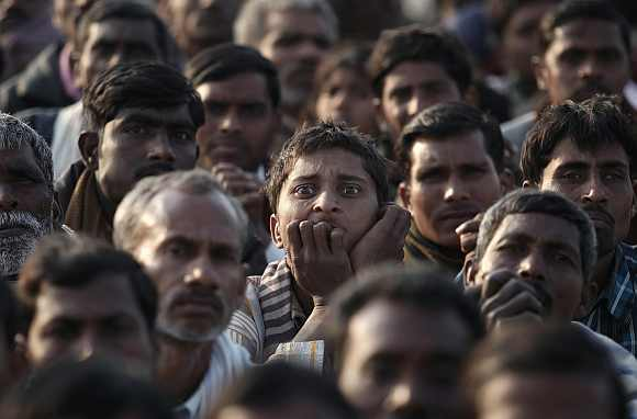 Supporters of Rahul Gandhi listen intently as he delivers a speech at an election campaign rally at Hardoi district