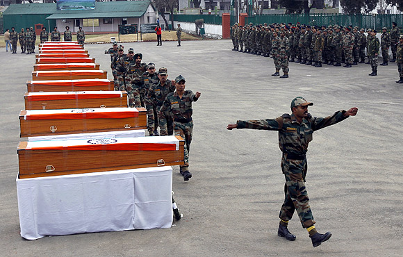 Army soldiers march in front of coffins containing bodies of colleagues killed in avalanches