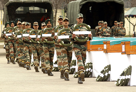 Army soldiers carrying wreaths walk in front of coffins containing the bodies of colleagues killed in avalanches