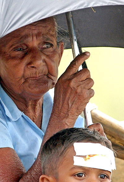 A file photo of an elderly woman waiting for transportation with a boy as they flee from their houses  in Trincomalee