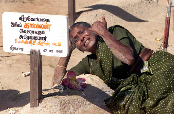 A mother cries on top of her son's grave at a cemetary in Mullathivu