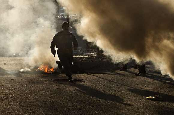An Afghan policeman runs for cover during clashes with protesters in Kabul