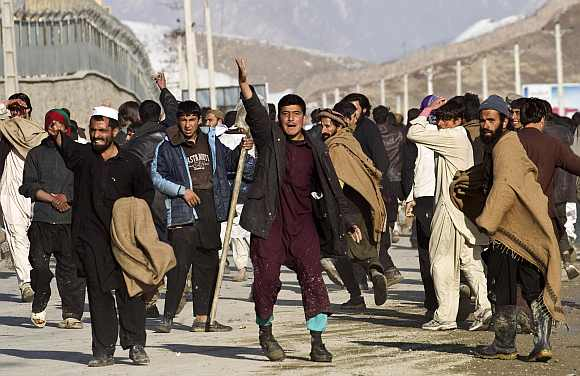 Afghan protesters gesture towards police in Kabul. Two protesters were shot dead in separate rallies in Kabul on Friday over the burnings of the Quran at a NATO base