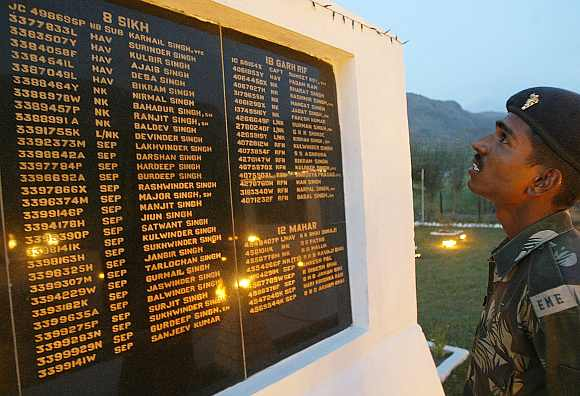 A soldier looks at the names of fallen colleagues at a war memorial during Vijay Diwas or Victory Day celebrations in Drass. The Indian army commemorates Vijay Diwas in memory of their more than 500 colleagues who were killed during the Kargil war with Pakistan