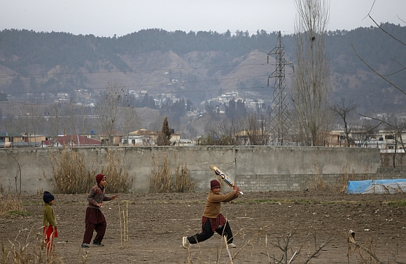 Children play cricket near the boundary wall of the building where bin Laden was killed, after it was demolished in Abbottabad