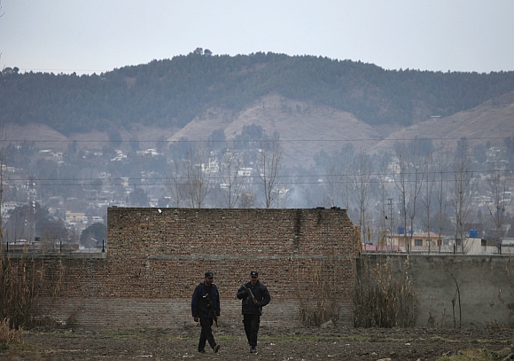 Policemen walk past the boundary wall of the building where bin Laden was killed after it was demolished in Abbottabad
