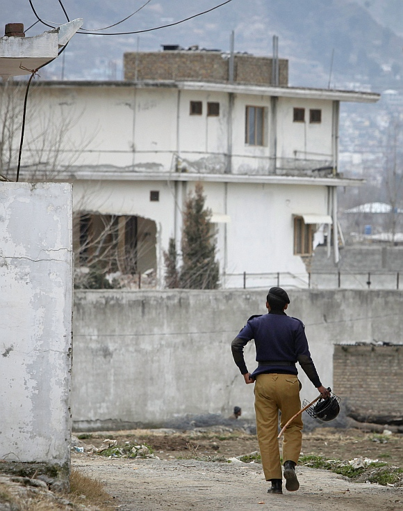 A policeman walks towards the partially demolished compound