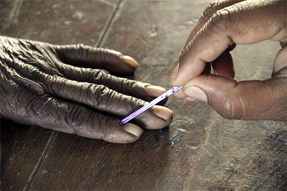 A voting official marks the finger of a voter inside a polling booth in UP
