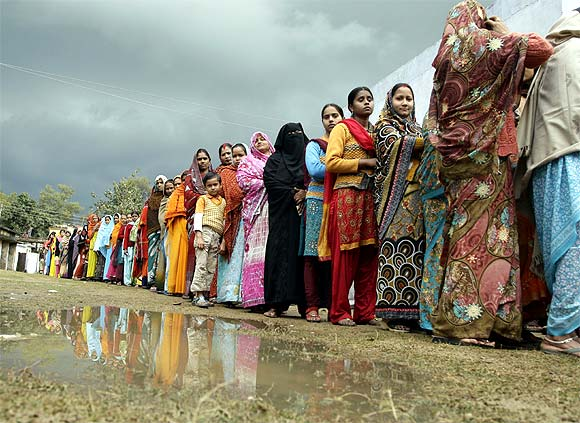 Voters line up in a queue outside a polling booth to cast their vote during the state assembly election