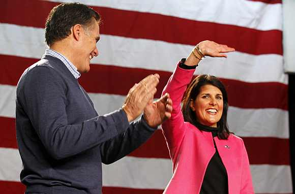 Republican presidential candidate and former Massachusetts Governor Mitt Romney applauds South Carolina Governor Nikki Haley as she is introduced to address a campaign rally at Pinkerton Academy in Derry, New Hampshire