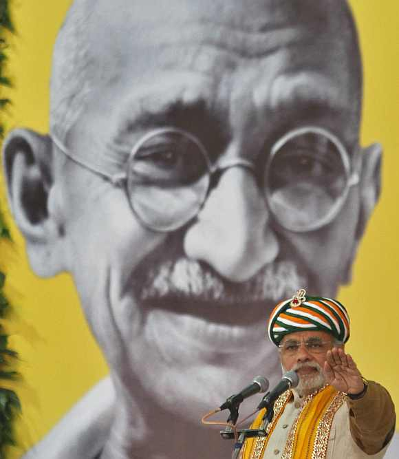 Gujarat's CM Narendra Modi addresses a gathering in front of a portrait of Mahatma Gandhi during his day-long fast at Godhra