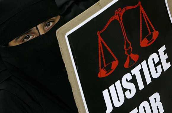 A veiled Muslim woman holds a placard during a protest