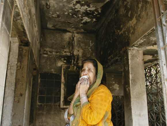 A survivor cries inside her house that was burnt and damaged during the Godhra riots during the commemoration of its 10th anniversary, in Ahmedabad