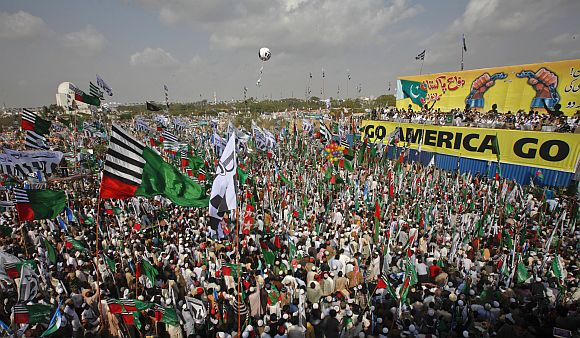 Hundreds of supporters of different religious and political parties hold their parties flags while taking part in an anti-American rally organised by the Difa-e-Pakistan Council in Karachi