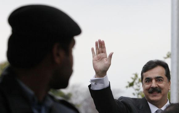A policeman looks towards Pakistan's Prime Minister Yusuf Raza Gilani waving