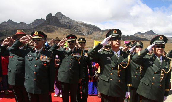 Indian and Chinese soldiers salute during celebrations to mark the 60th anniversary of the founding of the People's Republic of China, at the Indo-China border, near Tawang