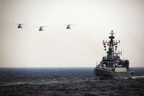 Helicopters accompany the Chinese Jiangwei II naval frigate 'Mianyang' during an international fleet review in Qingdao