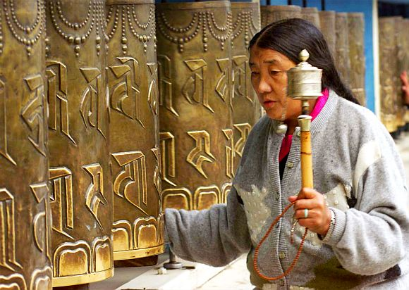 A Tibetan refugee moves prayer wheels at a monastery in Dharamsala