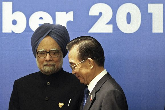 China's Premier Wen Jiabao walks past PM Singh ahead of a photo opportunity during 5th East Asia Summit in Hanoi, on October 30, 2010.