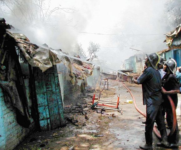 Firemen fight a blaze in a riot-hit neighbourhood of Ahmedabad, on May 11, 2002.