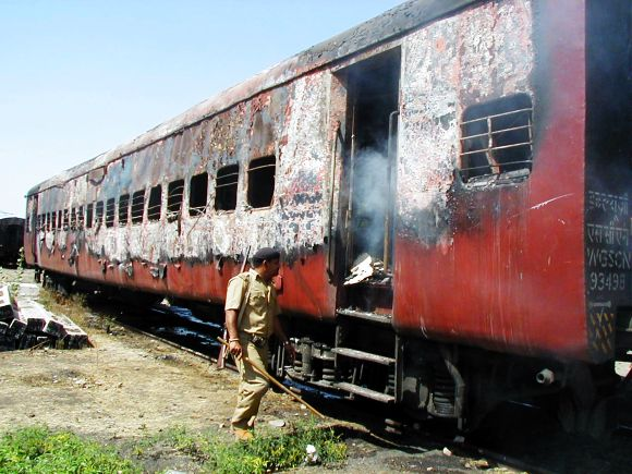Policeman walks towards the entrance of a carriage of Sabarmati Express train in Godhra