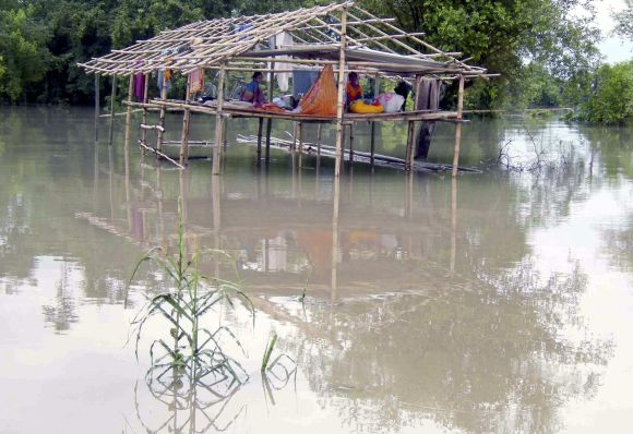 Flood-affected people sit in a damaged hut as they wait for relief supplies after an embankment of river Brahmaputra broke in Arunachal