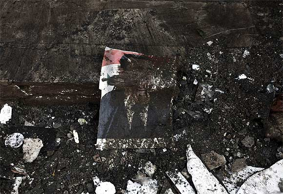 A defaced poster of President Bashar al-Assad is seen on the ground after heavy shelling by government forces in Sermeen