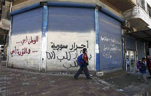 A schoolboy walks past graffiti that reads 'Syrian free people, Bashar is a dog and son of dog, home is my father and revolution is my mother' in Binnish