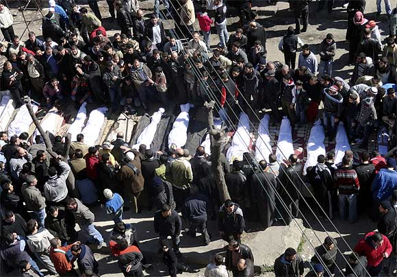 Syrians attend a mass funeral for more than a dozen of people, whom anti-government protesters said were killed during clashes with Syrian forces, at Khaldiyeh area in Homs city