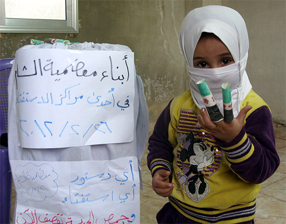 A child is seen during a protest against Syria's President Bashar Al-Assad and against voting for a referendum on a new constitution in Mouadamia near Damascus