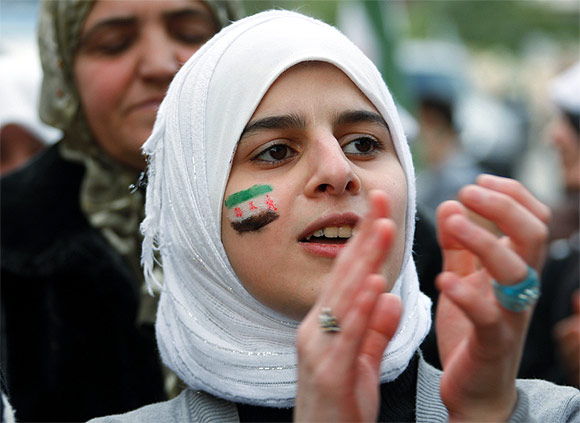 A Syrian refugee, whose face is painted with a Syrian opposition flag, takes part in a protest, calling for international protection for Syria's anti-government protesters and better living conditions for Syrian refugees in Lebanon, in front of the Red Cross offices in Tripoli, northern Lebanon