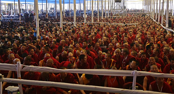 Buddhist monks listen to a teaching session being addressed by the Dalai Lama on the first day of the Kalachakra festival in Bodhgaya