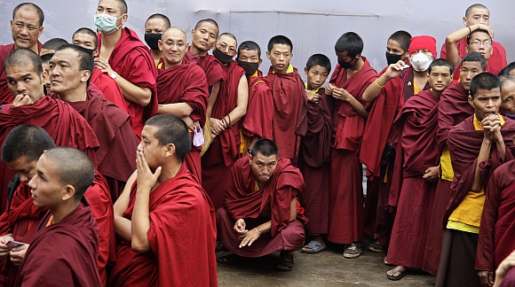 Buddhist monks wait to enter the complex to attend a teaching session being addressed by the Dalai Lama on the first day of the Kalachakra festival