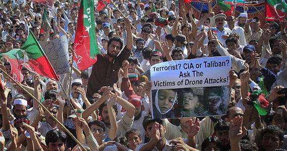Supporters of Pakistan Tehreek-e-Insaf wave party flags and hold placards while listening Khan lead a protest against drone attacks in Peshawar
